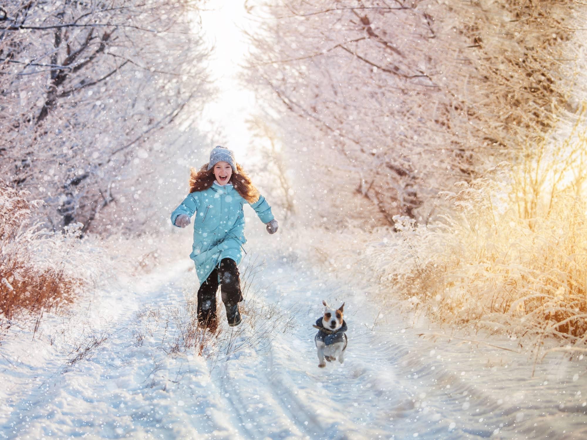 petite fille qui court avec son chien en hiver